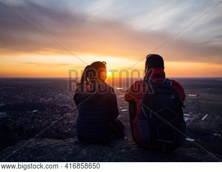 Couple enjoying sunset from mountain view. Young happy couple enjoying sunset over small town. Beautiful people. Happy people. Happy couple in city sunset. Young happy couple . People in sunset. People. Sunset. City life.