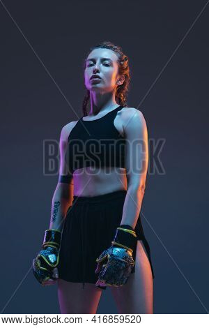 Caucasian Female Mma Fighter Posing Isolated Over Blue Background In Neon Light