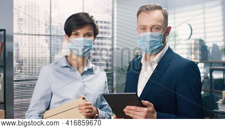 Portrait Of Young Happy Caucasian Male And Female Co-workers In Medical Masks Standing In Cabinet An