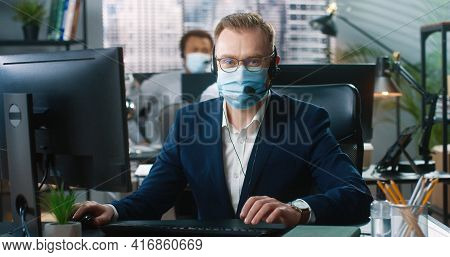 Portrait Of Young Busy Caucasian Male Employee In Medical Mask Sitting At Office In Headset, Typing