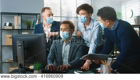 Portrait Of Young Mixed-race Colleagues In Medical Masks Talking And Working In Cabinet. Male And Fe