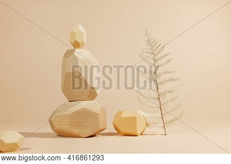 Composition of geometric wooden balancing stones with plant. Concept of balance, eco frendly. Pastel background with copy space.