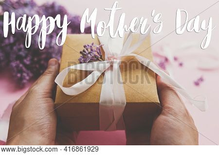 Happy Mother's Day Greeting Card. Happy Mother's Day Text And Hands Giving Gift Box With Ribbon And