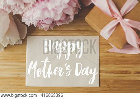 Happy Mother's Day. Happy Mother's Day Text On Card And Peony Bouquet, Gift Box On Wooden Table Top