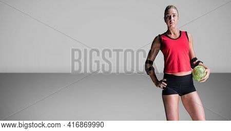 Blonde caucasian woman holding a softball, looking into camera, over grey background. sports concept, digitally generated image