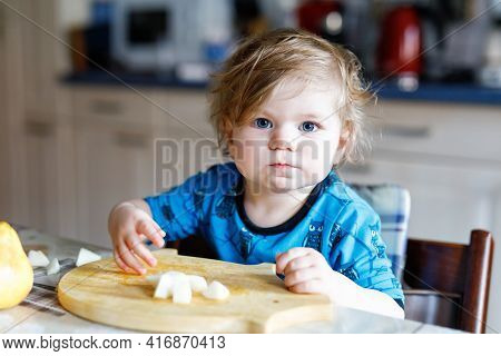 Cute Adorable Toddler Girl Eating Fresh Pear. Hungry Happy Baby Child Of One Year Holding Fruit. Gir