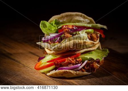Homemade flatbread sandwich, kebab or doner with chicken meat, lettuce and vegetables on wooden background