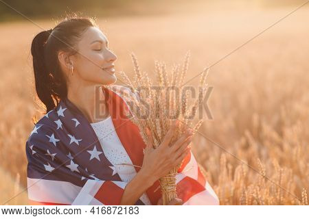 Woman With American Flag And With A Sheaf Of Ears In Wheat Field At Sunset. 4th Of July. Independenc