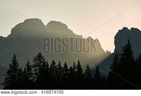 Sunlight beam shining through rock formations on a misty morning