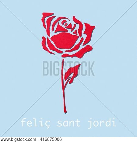 a rose, made with cutouts of a red paper, on a blue background and the text happy saint george day in catalan, when it is tradition to give red roses in catalonia, spain
