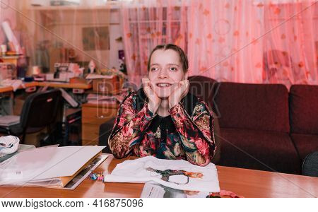 A Disabled Girl With Slanted Eyes Sits At A Table And Smiles. People With Disabilities.