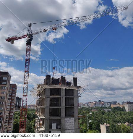 A High-rise Building Under Construction Against A Beautiful Blue Sky. High-rise Crane On Constructio