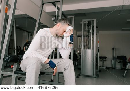Very Tired After An Intense Workout, A Man Sits In The Gym Wiping Sweat From His Face With A Towel.
