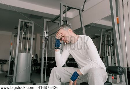A Tired Athlete After A Hard Workout Sits And Rests With His Hand On His Head. Long-term Cardio Trai