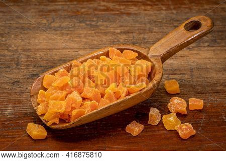 dried mango fruit diced - rustic wooden scoop on a weathered wood background