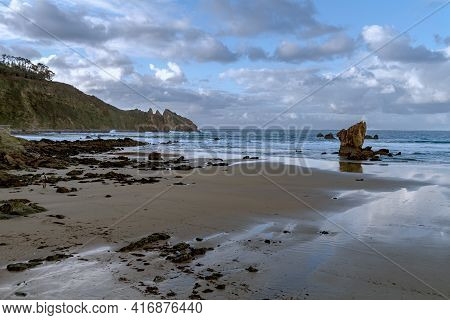 Beautiful View Of Lonely Beach With Rock Formations In The Spanish Area Of Asturias In Winter At Low