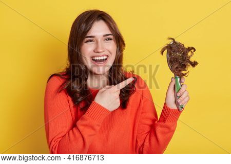 Dark Haired Girl In Orange Sweater Holding Comb With Lost Hair And Pointing With Index Finger At It,