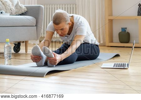 Senior Woman Stretching, Online Training With Laptop In Living Room. Exercising For Health. Well-bei