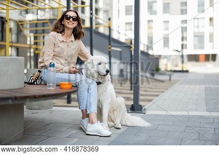 Cheerful Woman Sitting On Bench With Big White Dog In The Courtyard Of The Residence. Animal Lover,