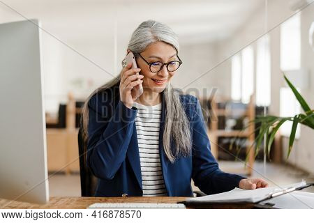 The happy Asian woman talking on the phone and looking at papers on the tablet in a light office