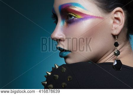 Creative Makeup. Female Model With Colored Artistic Make-up, Isolated Blue Background.