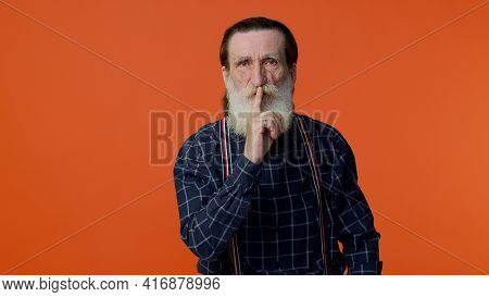 Shh Be Quiet Please. Elderly Bearded Gray-haired Man Presses Index Finger To Lips Makes Silence Gest