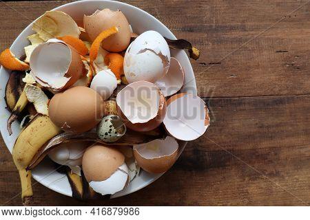 Banana Skin, Eggshell, And Orange Peels In White Bowl On Wooden Table Background. Using Kitchen Scra