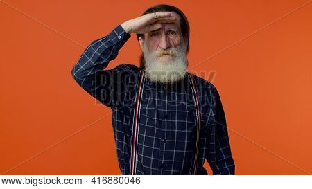 Here You Are, Found You. Mature Old Gray-haired Grandfather Holding Hand Above Eyes Forehead, Peerin