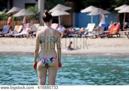 Woman In Bikini Standing On Background Of Sea Beach And Tanning People. Summer Holiday On Tourist Re