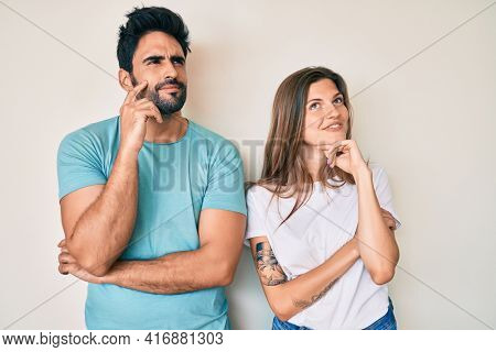 Beautiful young couple of boyfriend and girlfriend together with hand on chin thinking about question, pensive expression. smiling and thoughtful face. doubt concept.