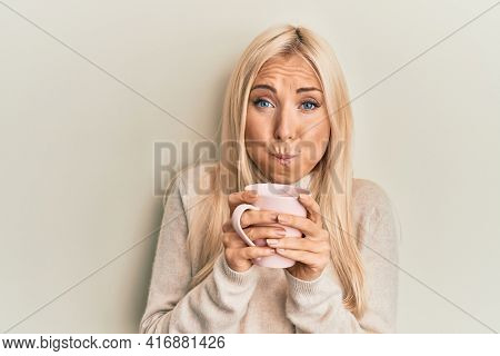 Young blonde woman drinking a cup of coffee puffing cheeks with funny face. mouth inflated with air, catching air.