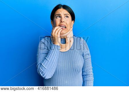 Beautiful brunette woman wearing cervical collar looking stressed and nervous with hands on mouth biting nails. anxiety problem.