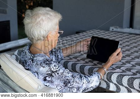 Gray-haired And Short-haired Old Woman With Glasses. The Woman Is Alone. You Cant See His Face, Only