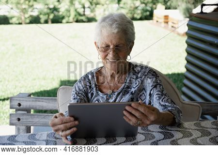 Gray-haired And Short-haired Old Woman With Glasses. The Woman Is Alone And Happy. The Old Lady Is L