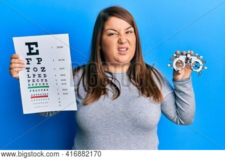Beautiful brunette plus size woman holding optometry glasses and eyesight test clueless and confused expression. doubt concept.