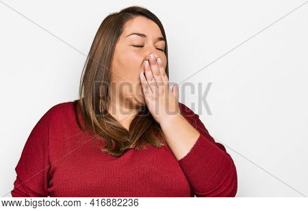 Beautiful brunette plus size woman wearing casual clothes bored yawning tired covering mouth with hand. restless and sleepiness.