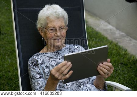 Older Lady With Short Gray Hair Wearing Glasses. The Old Woman Is Sitting In Her Lounge Chair And Sh