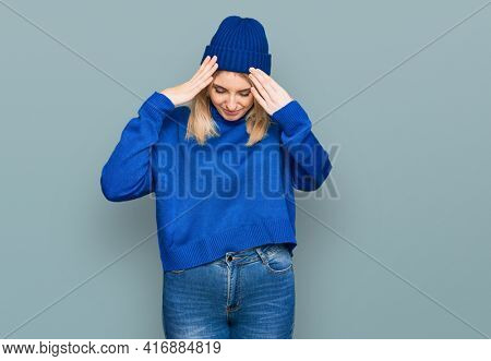 Young caucasian woman wearing wool winter sweater and cap suffering from headache desperate and stressed because pain and migraine. hands on head.