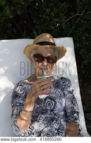 Short Gray-haired Adult Woman With Sunglasses And Hat. The Old Lady Is Drinking Mate And Is Sitting