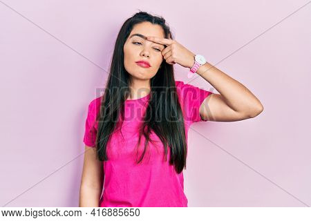 Young hispanic girl wearing casual pink t shirt pointing unhappy to pimple on forehead, ugly infection of blackhead. acne and skin problem