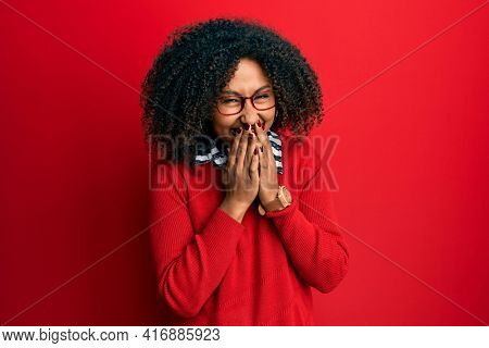 Beautiful african american woman with afro hair wearing sweater and glasses laughing and embarrassed giggle covering mouth with hands, gossip and scandal concept