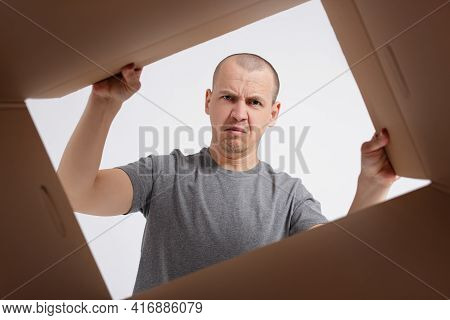 Young Disappointed Man Looking Inside The Box - View From The Box