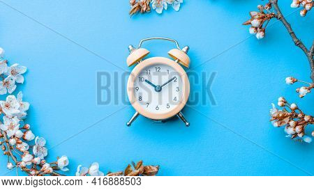 Spring Time Background. May Flowers And April Floral Nature With Alarm Clock On Blue. Branches Of Bl