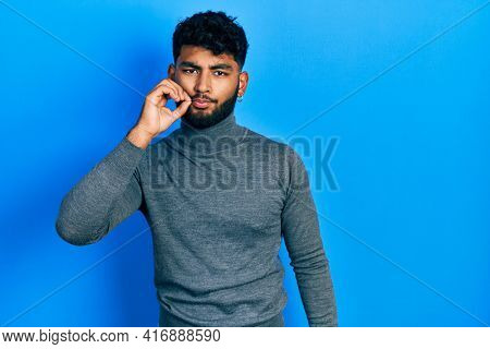 Arab man with beard wearing turtleneck sweater mouth and lips shut as zip with fingers. secret and silent, taboo talking