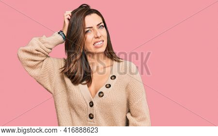 Young brunette woman wearing casual winter sweater confuse and wonder about question. uncertain with doubt, thinking with hand on head. pensive concept.
