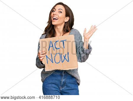 Young brunette woman holding act now banner celebrating victory with happy smile and winner expression with raised hands