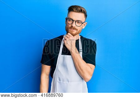Young redhead man wearing professional apron thinking concentrated about doubt with finger on chin and looking up wondering
