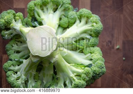 Selective Focus Broccoli Stalk On Wooden Blurred Background With Copy Space. Top View. Fresh Head Of
