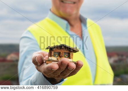 Selective Focus Close-up Of Miniature Tiny Wooden House Held By Old Male Builder Wearing Fluorescent