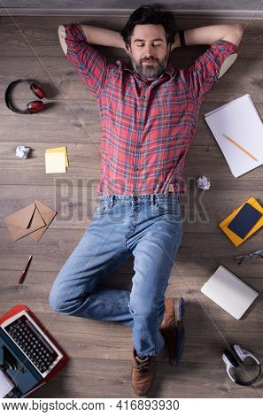 Man relaxing on floor thinking idea solitions. Student man lying top view. Creative inspiration study concept